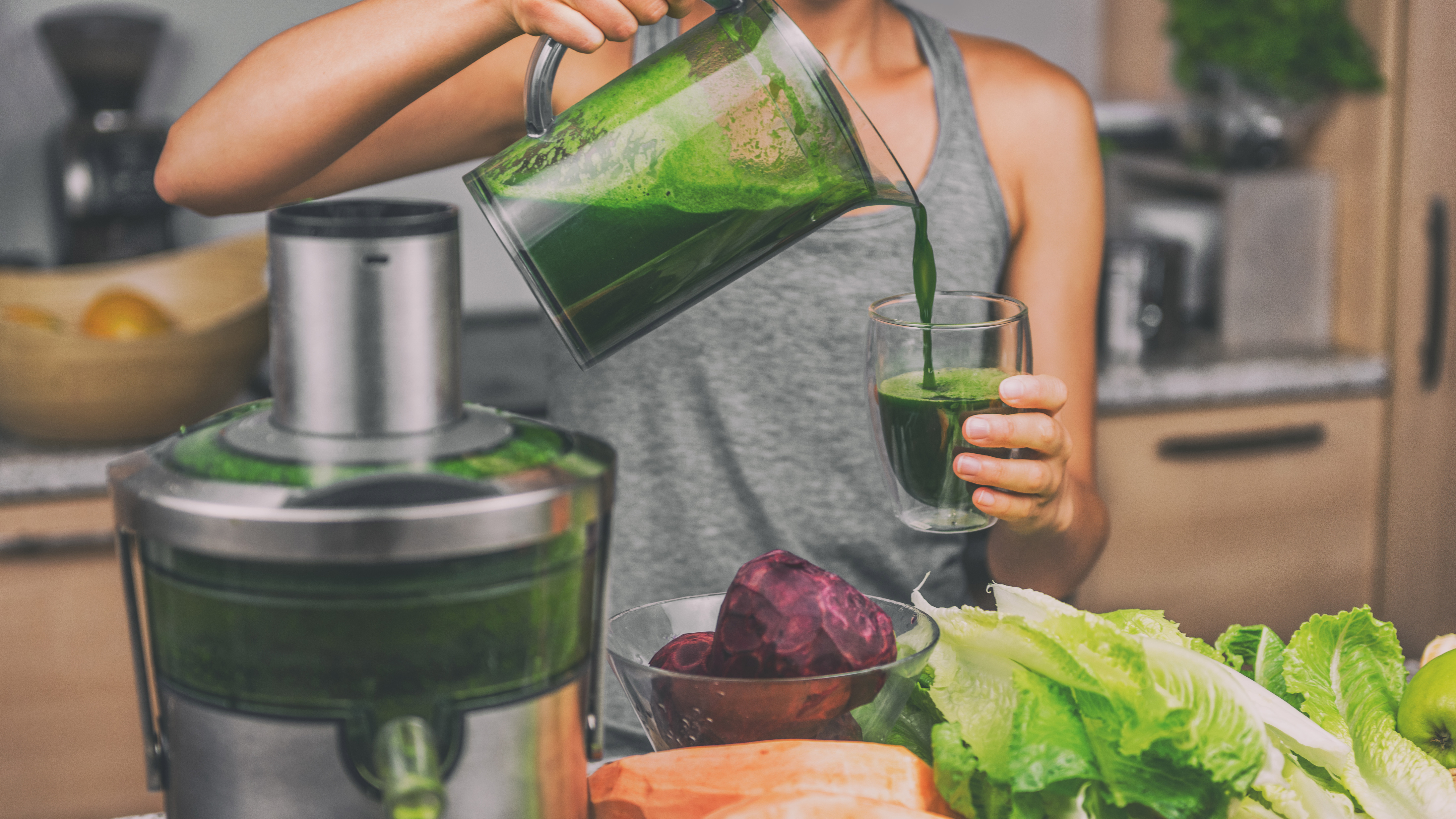 A woman making a healthy green juice in a juicer surrounded by vegetables